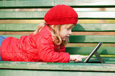Happy smiling little girl working with tablet pc — Stock Photo