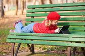 Klein meisje werken met de tablet pc in het park. — Stockfoto