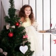 Happy elegant little girl decorating Christmas tree — Stockfoto