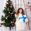 Happy little girl holding gifts near Christmas tree. — Stock Photo