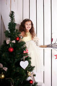 Happy elegant little girl decorating Christmas tree — Stock Photo