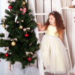 Happy  little girl decorate the Christmas tree.  — Foto de Stock