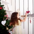 Happy little girl decorate Christmas tree and home. — Foto de Stock
