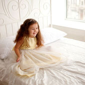 Little princess on a white bed. — Stock Photo