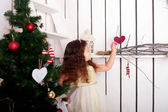 Happy little girl decorate Christmas tree and home. — Stock Photo