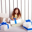 Happy smiling child holding gifts — Stock Photo