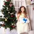 Happy smiling kid holding gifts near Christmas tree. — Stock fotografie