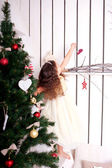 Happy little kid decorate the Christmas tree and home. — Stock Photo