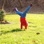 Little girl standing on hands upside down — Stock Photo