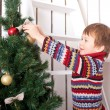 Happy kid decorating the Christmas tree with balls.  — Stock Photo