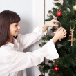 Charming woman decorating the Christmas tree with balls. — Foto de Stock