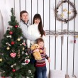 Happy family near the Christmas tree. — Stock Photo