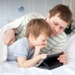 Father and son playing on tablet  — Stock Photo