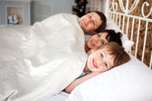 Happy family lying in bed, family concept. — Stock Photo
