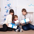 Stock Photo: Young family holding gifts near the fireplace