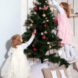 Two little girls decorating the Christmas tree. — ストック写真