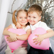Little kids hugging and holding heart balloons. — Stock Photo