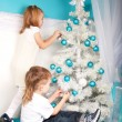 Little boy and girl decorating the Christmas tree — Stock Photo #37325617