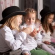 Kids in black hats drink milk. — Stock Photo #39371871