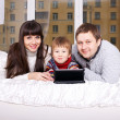 Happy family using the tablet lying on bed. — Stock Photo