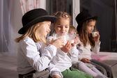 Kids in black hats drink milk. — Stockfoto
