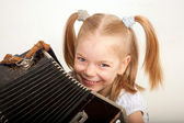 Smiling child with accordion. Little musician. — Stock Photo
