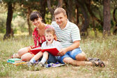 Happy family reading together. — Stock Photo