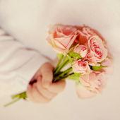 Newborn baby hand holding bouquet — Stock Photo