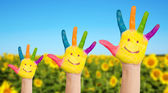 Three painted hands of family on sunflowers field — Stock Photo