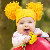 Baby in yellow knitted cap with dandelions  — ストック写真