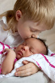 Multiracial family concept. Brother kissing newborn — Стоковое фото