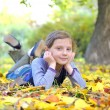 Little girl lays on leaves — Stock Photo #13487377