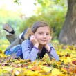 Little girl lays on the leaves — Stock Photo