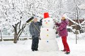 Snögubbe och barn — Stockfoto