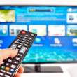 Smart tv and hand pressing remote control — Stock Photo #16296813