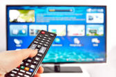 Smart tv and hand pressing remote control — Stockfoto