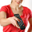 Young girl watching tv using a remote control — Stock Photo