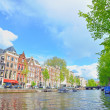 Traditional Houses and house boat along canal in Amsterdam - Stock Photo