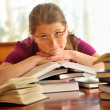 Teen girl learning at the desk, looking up — Stock Photo