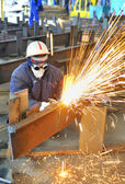 Worker using torch cutter to cut through metal — Stock Photo