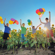 Happy childrens jumping on meadow with balloons — Stock Photo #27613373