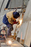 Worker grinding metal inside of shipyard — Stock Photo