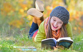 Beautiful girl with book in autumn park — Stock Photo