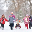 Group of children and mother playing on snow in winter time — Stok fotoğraf