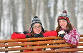 Dos jóvenes amigas juntos sentados en un banco del parque — Foto de Stock