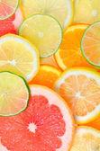 Sliced citrus fruits background — Stock Photo