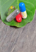 Vitamins, tablets and pills on green leaf — Stock Photo