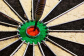 Dart in the centre bulls eye — Stock Photo