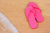 Summer vacation background flip flops on beach — Stock Photo