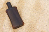 Sun tan oil on sand — Stock Photo